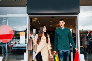 Couple walking out of store with shopping bags